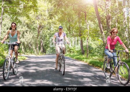 Tre donna matura in bicicletta lungo la strada di campagna Foto Stock