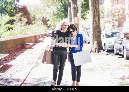 Giovane donna e suo mentore shopping e ridere su Street, New York City, Stati Uniti d'America Foto Stock
