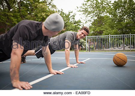 Giovani uomini facendo premere up sul campo di pallacanestro Foto Stock