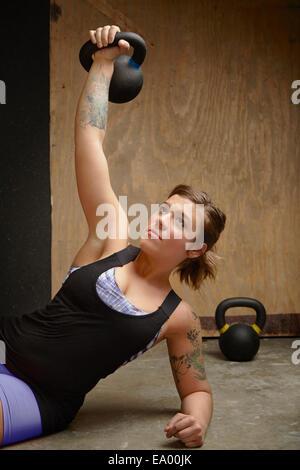 Giovane donna kettlebell sollevamento in palestra Foto Stock