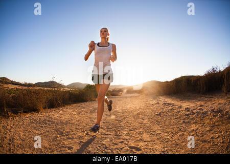 Giovane donna jogging sul percorso soleggiato, Portland, CA, Stati Uniti d'America