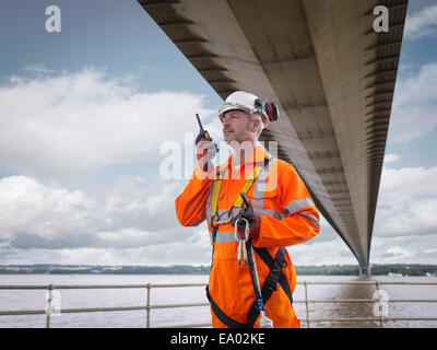 Lavoratore a ponte utilizzando un walkie-talkie sotto sospensione ponte Humber Bridge Regno Unito è stato costruito Foto Stock