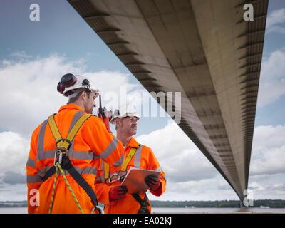 Ponte dei lavoratori che utilizzano walkie-talkie sotto sospensione ponte Humber Bridge Regno Unito è stato costruito Foto Stock