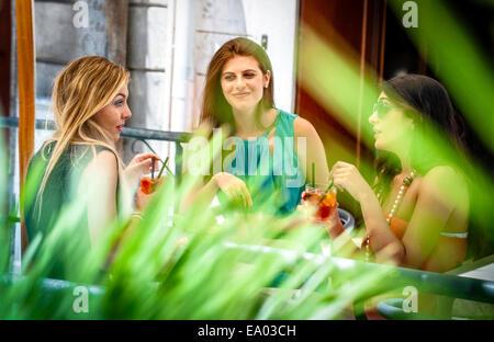 Tre giovani amici di sesso femminile avente cocktail al cafè sul marciapiede, Cagliari, Sardegna, Italia Foto Stock