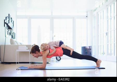 Metà adulto madre la pratica dello yoga con toddler figlia sulla parte superiore della sua Foto Stock