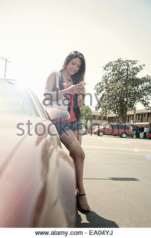 Giovane donna in piedi accanto a AUTO, utilizzando smart phone Foto Stock