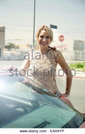 Ritratto di giovane donna in piedi accanto a AUTO Foto Stock