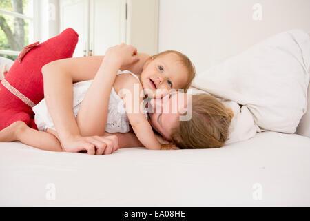 Madre abbracciando la nostra bambina sul letto Foto Stock
