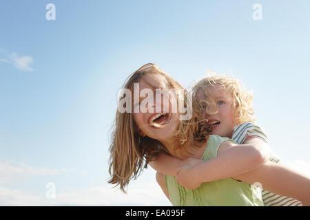 Basso angolo vista della ragazza dando sorella piggy back a costa Foto Stock