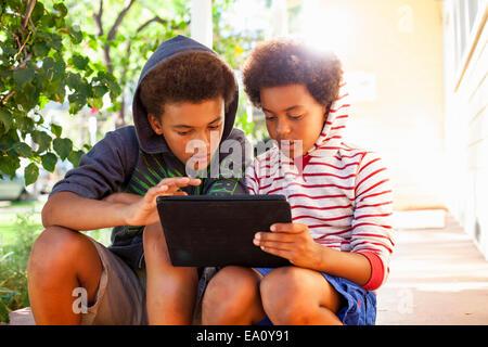 Due fratelli mediante schermo tattile sulla tavoletta digitale in giardino Foto Stock
