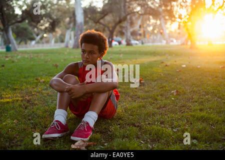 Triste cerca ragazzo seduto in posizione di parcheggio Foto Stock