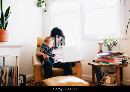 Madre utilizzando laptop con figlio al giro Foto Stock