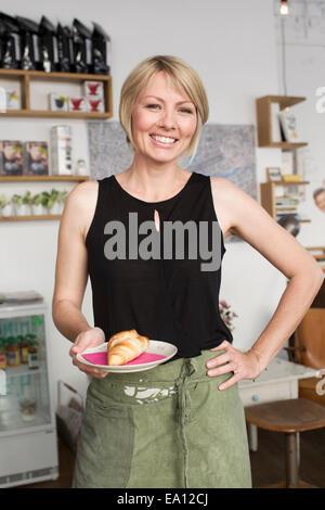 Metà donna adulta tenendo la piastra con croissant al cafe Foto Stock