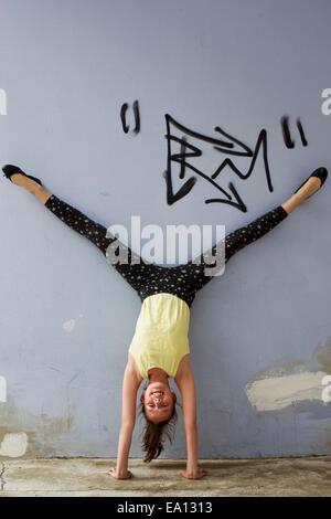 Ragazza adolescente facendo handstand contro la parete Foto Stock