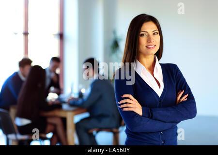 Imprenditrice sorridente in piedi con le braccia incrociate di fronte ai colleghi Foto Stock