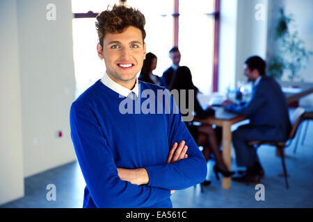 Imprenditore sorridente in piedi con le braccia incrociate di fronte ai colleghi Foto Stock