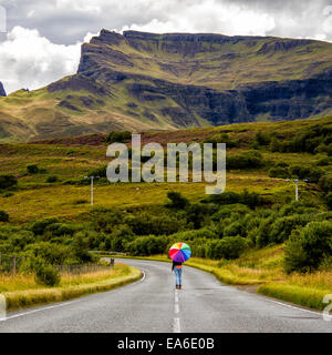 Regno Unito, Scozia, Donna con ombrellone sulla strada di campagna Foto Stock