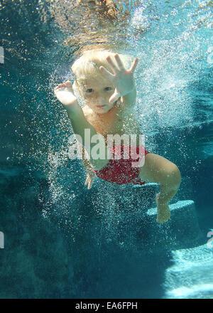 Ragazzo di nuoto sott'acqua in piscina Foto Stock