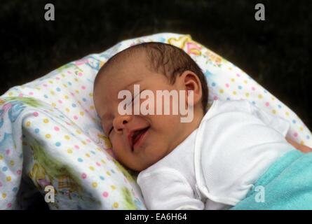 Neonato bambino addormentato nella sua portante ha un bel sorriso sul suo volto. Egli sembra essere di ridere. Foto Stock