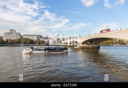 Il fiume Tamigi e Waterloo Bridge con red London bus dalla banca del sud del terrapieno con riverboat e Shell Mex Foto Stock