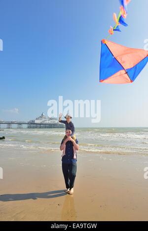 Il nonno con il nipote volare un aquilone sulla spiaggia a Eastbourne. East Sussex. Regno Unito Foto Stock