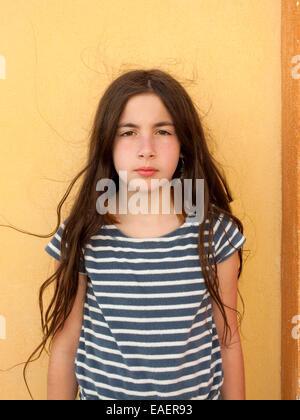 Ragazza giovane con espressione seria e capelli crespi Foto Stock