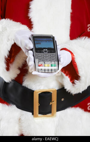 Close Up di Santa Claus tenendo il lettore di carte di credito Foto Stock