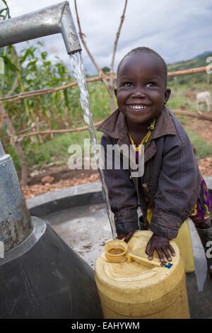Tre anni di Abigail Chemtai è il primo ad attingere acqua da una nuova ben installato nel villaggio Sukuroi, Bukwo Foto Stock