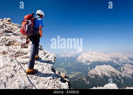 L'alpinista salendo la Via Ferrata Marino Bianchi arrampicata sul Monte Cristallo e si affaccia sulle Tofane Montagne Foto Stock