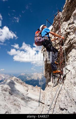 L'alpinista salendo la Via Ferrata Ivano Dibona arrampicata sul Monte Cristallo, provincia di Belluno, Italia Foto Stock