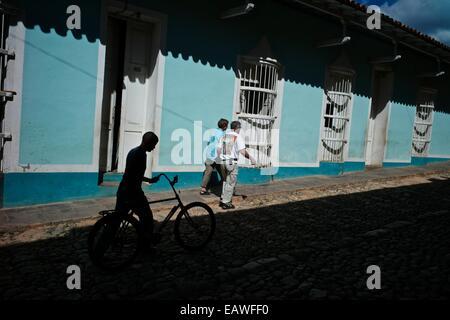 I pedoni passano un muro colorato nella città coloniale di Trinidad. Foto Stock