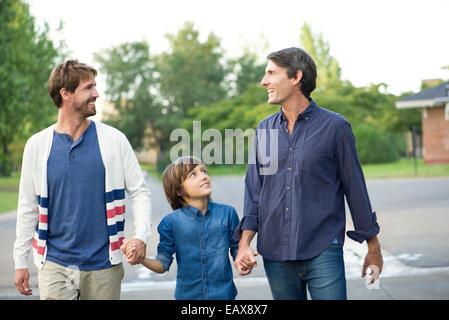 Padri tenendo le mani con figlio all'aperto Foto Stock