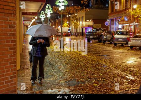 Donna sul cellulare con ombrellone sulla strada del centro sulla notte piovosa-Victoria, British Columbia, Canada. Foto Stock