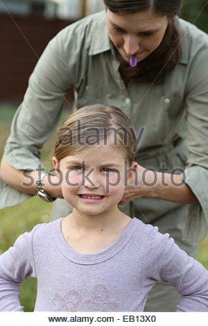 Una madre che fissa la sua figlia di capelli. Foto Stock