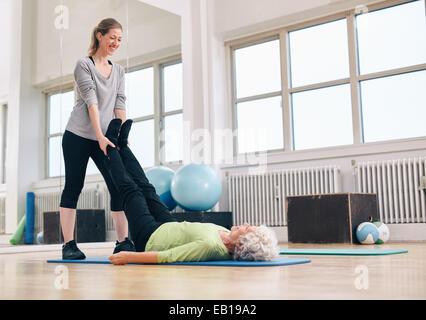 Personal trainer lavora con il cliente sul tappeto di esercizio in palestra. Istruttore tenendo le gambe della donna Foto Stock