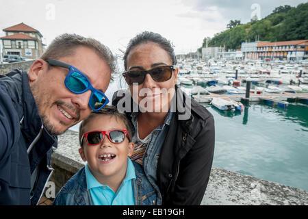 Famiglia avente fun indossando occhiali da sole & agitando per una telecamera tenendo selfie fotografia nel periodo delle vacanze estive