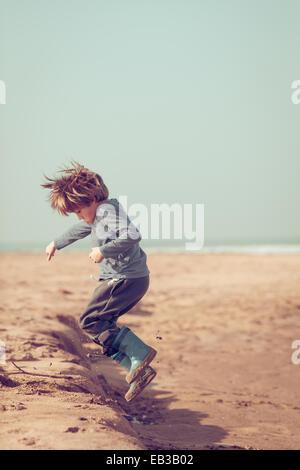 Ragazzo saltando in sabbia sulla spiaggia, Marocco Foto Stock