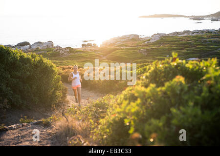 Sentiero donna che corre lungo la costa, Corsica, Francia