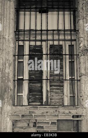 Parzializzato decadendo finestra con un arrugginimento griglia metallica. L'Avana Cuba. Foto Stock