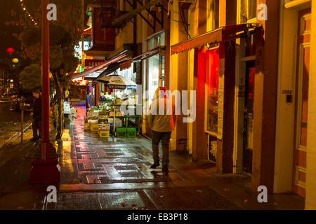 Uomo con cappuccio sulla camicia fino a Piedi di Chinatown sulla notte piovosa-Victoria, British Columbia, Canada. Foto Stock