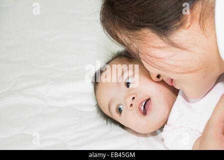 Felice famiglia allegra. Asian il bambino e la madre baciare, ridendo e abbracciando Foto Stock