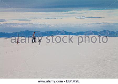 Un uomo e sua figlia a piedi il loro cane attraverso le dune di sabbia bianca, con il San Andres montagne in distanza. Foto Stock