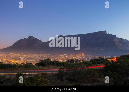 La Montagna della Tavola al tramonto con il passaggio di auto e luci della città Foto Stock