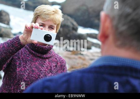 Donna di prendere foto di un uomo con Smart Phone Foto Stock