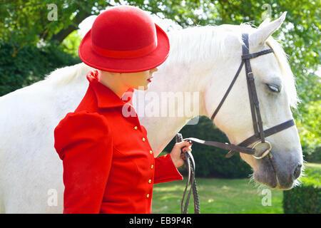 Donna in rosso vestito equestre con cavallo Foto Stock