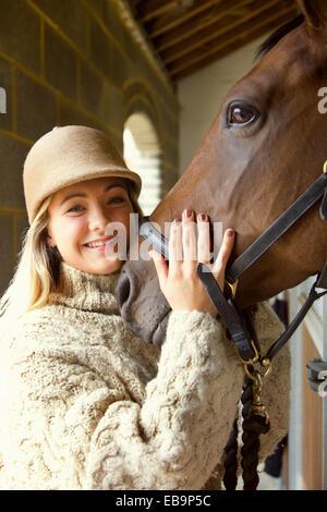 Sorridente giovane donna Stroking testa di cavallo Foto Stock