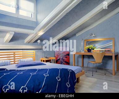 Gli scatti in interni di una moderna mansarda con in primo piano un tessuto divano sullo sfondo - Pareti blu camera da letto ...