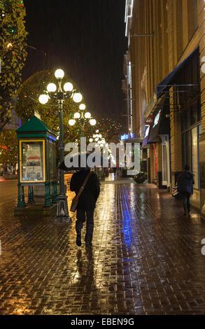 Uomo che cammina nel centro cittadino di Victoria sulla notte piovosa-Victoria, British Columbia, Canada. Foto Stock