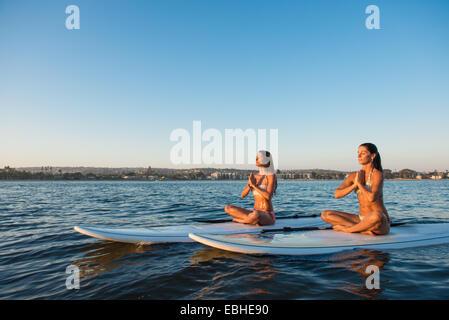 Due donne nella posizione del loto sul paddleboards, Mission Bay, San Diego, California, Stati Uniti d'America Foto Stock