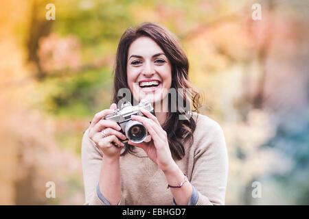 Ritratto di sorridente giovane donna con fotocamera reflex in foresta di autunno Foto Stock
